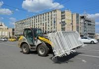 Фронтальный погрузчик Kramer Allrad 480 транспортирует ограждения . Москва, Тверская улица