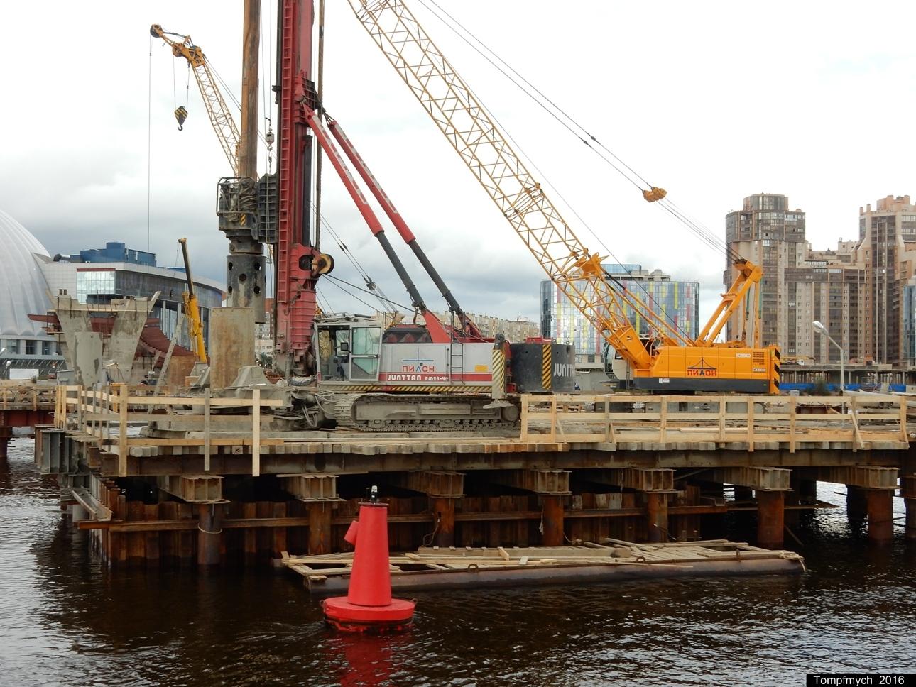 Буровая установка Junttan PM28-40 и кран Kobelco CKS600 на строительстве пешеходного моста на Крестовский остров. Санкт-Петербург, р. Большая Нева