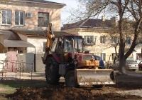 Трактор ЮМЗ-6АКМ-40.2, с обратной лопатой, на работе, закапывает яму, разрытую для установления новых труб. #1601 КВ 82. Крым, Евпатория, улица Дмитрия Ульянова
